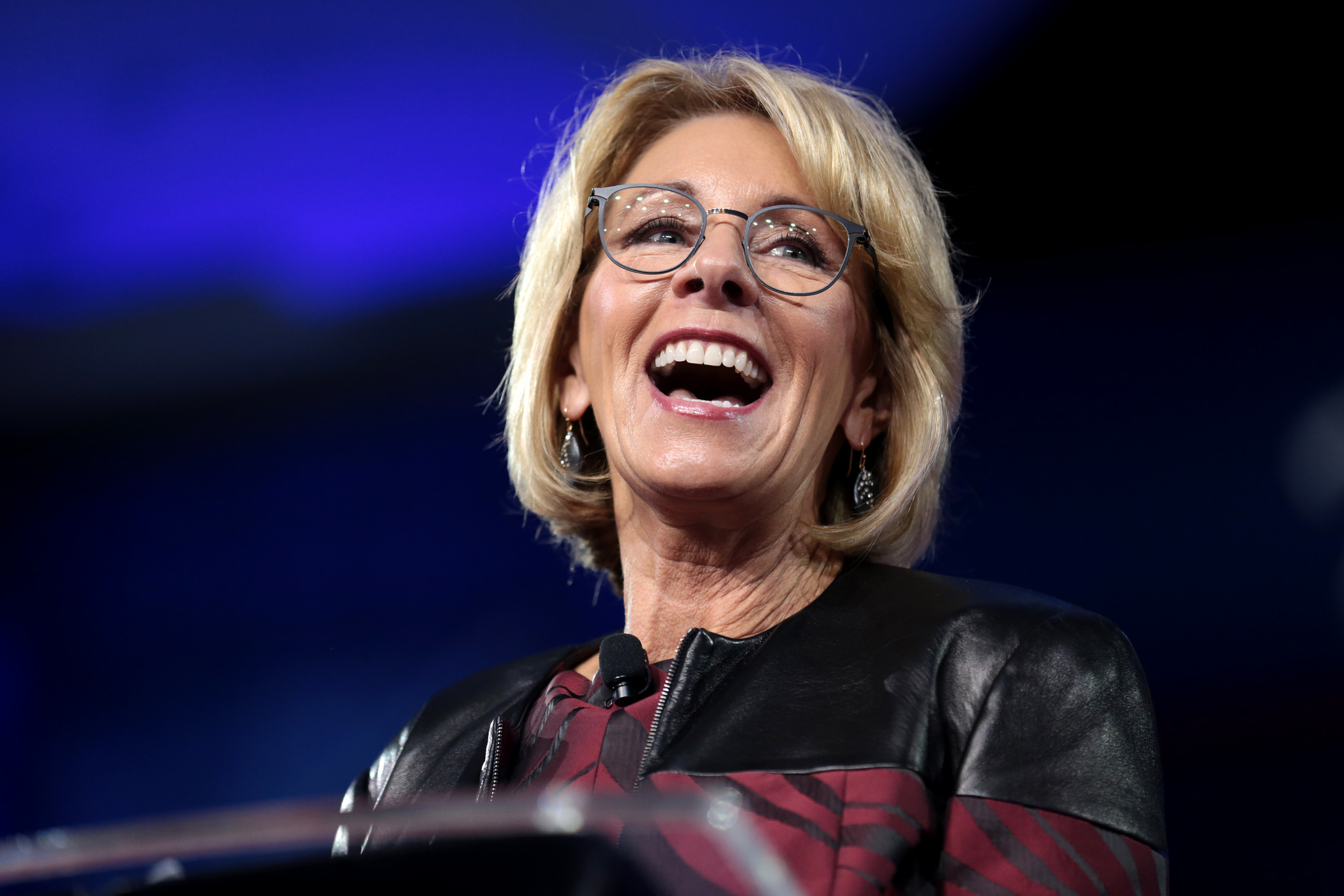 Betsy DeVos standing at a podium laughing