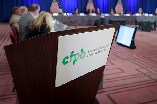 """Podium with a sign on it that reads """"CFPB Consume Financial Protection Bureau"""""""