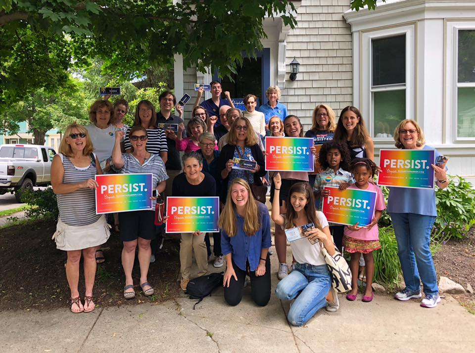 """Group of canvassers who attended a canvassing event in Newburyport holding rainbow signs that say """"PERSIST"""""""