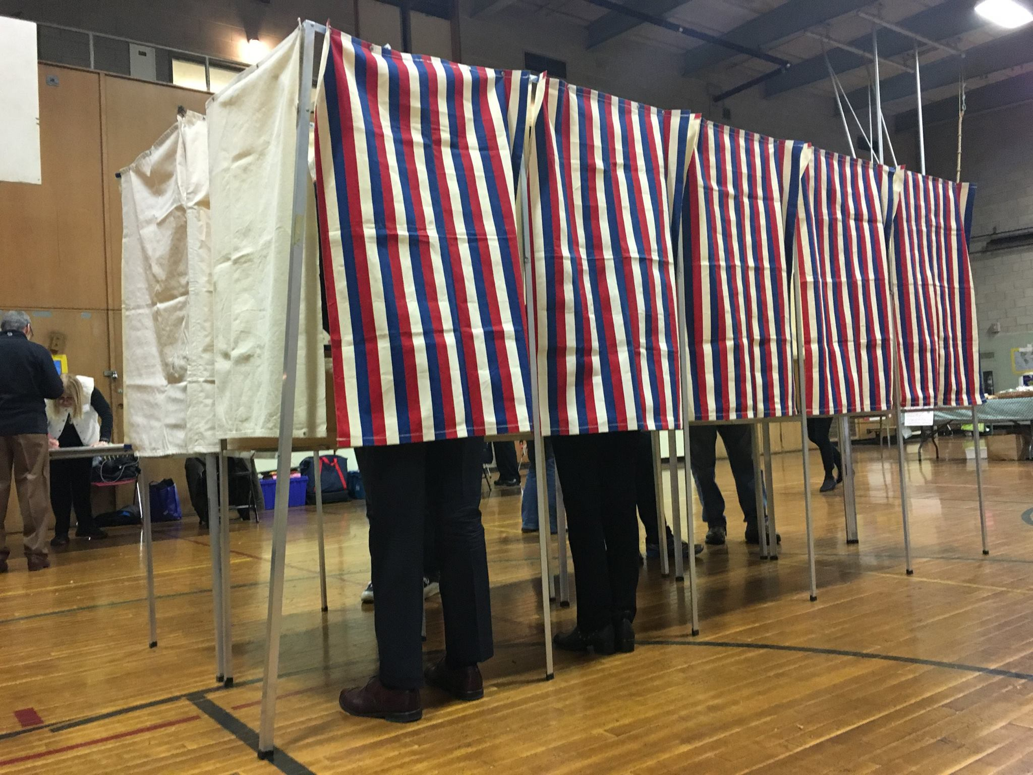 People standing in voting booths with striped curtains