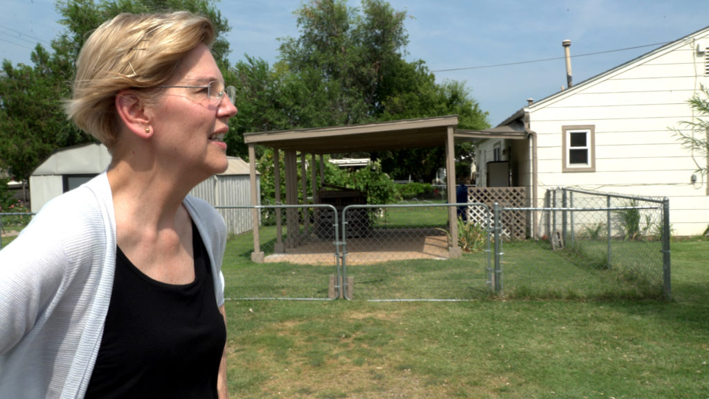 Elizabeth Warren in profile looking off into the distance in a neighborhood in Oklahoma