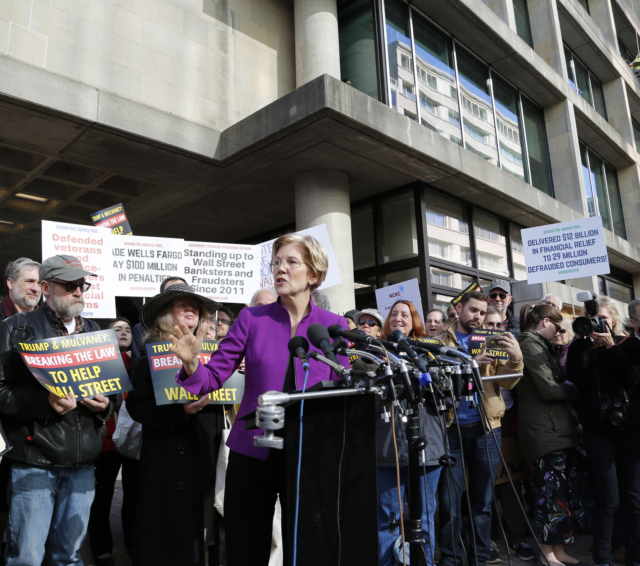Elizabeth Warren speaking from a podium at a rally for the CFPB