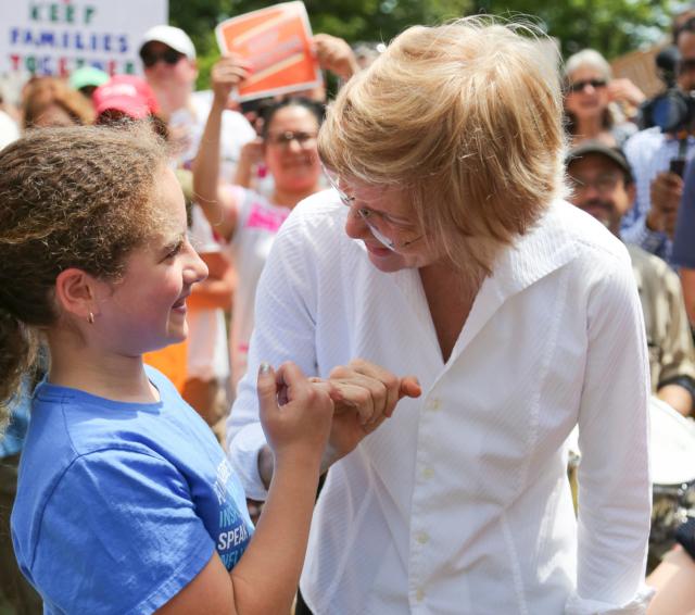 Elizabeth Warren pinky swearing with a young girl